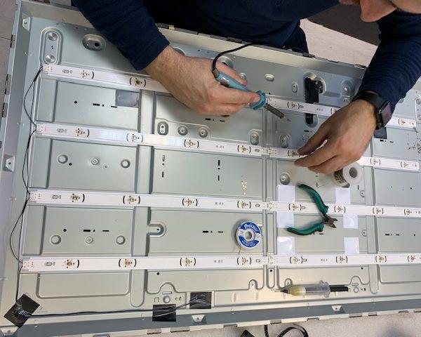 Мастер ремонтирует телевизор LG